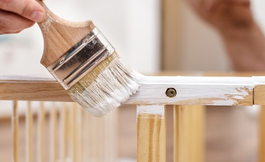 Man painting wood furniture with a brush and paints, close-up